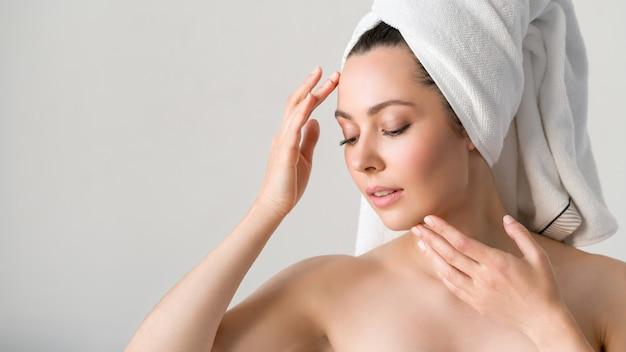 Młoda piękna kobieta z idealną skórą, dotykając jej twarzy. koncepcja kosmetologii, piękna i spa.