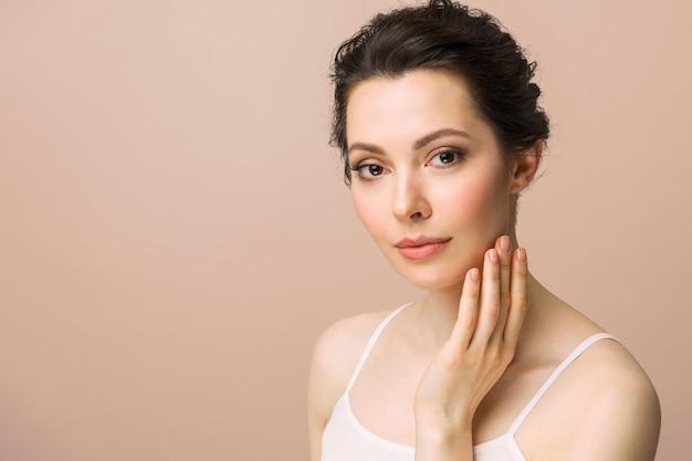 Młoda piękna kobieta z idealną skórą dotykającą jej koncepcji kosmetologii twarzy i spa