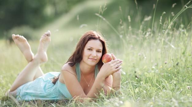Młoda piękna kobieta z jabłkiem odpoczywa na świeżej zielonej trawie .zdjęcie z miejscem na kopię