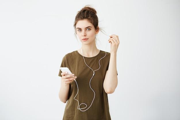Młoda piękna kobieta z kok uśmiechając się słuchanie muzyki w słuchawkach