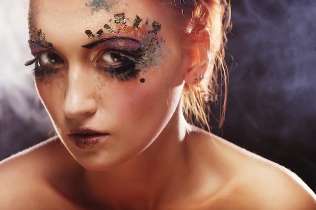 Młoda piękna kobieta z kolorowym jaskrawym makijażem
