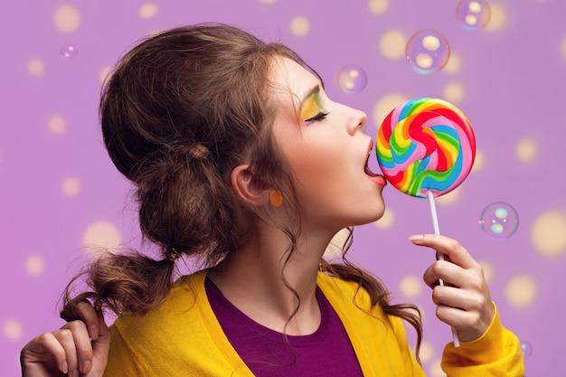 Młoda piękna kobieta z kolorowym lizakiem