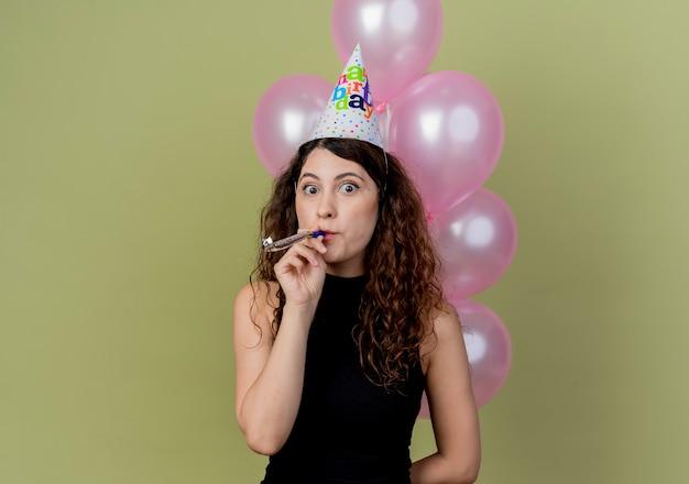 Młoda piękna kobieta z kręconymi włosami w czapce świątecznej, trzymając balony dmuchanie w gwizdek szczęśliwy i pozytywny świętuje urodziny nad światłem