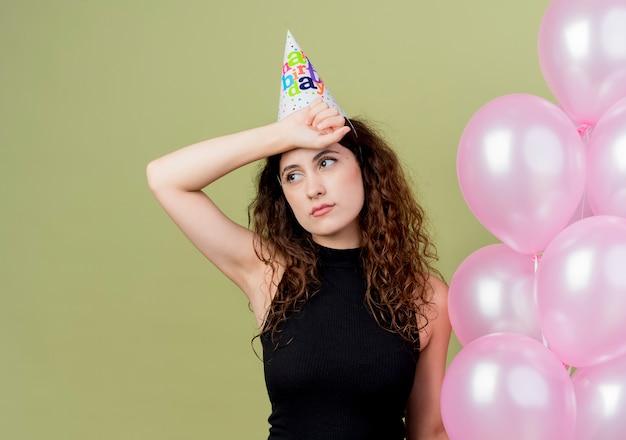 Młoda piękna kobieta z kręconymi włosami w czapce świątecznej, trzymając balony z powietrzem, patrząc na zmęczoną i znudzoną koncepcję przyjęcia urodzinowego stojącego nad ścianą światła