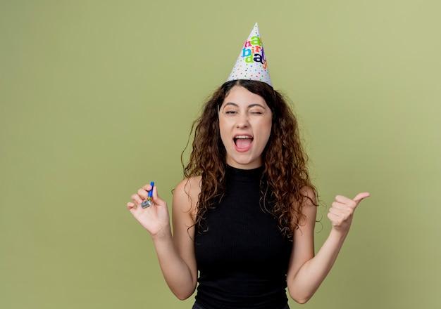 Młoda piękna kobieta z kręconymi włosami w czapce świątecznej, trzymająca gwizdek szczęśliwa i przekroczona, pokazująca kciuki do góry koncepcja przyjęcia urodzinowego stojącego nad jasną ścianą