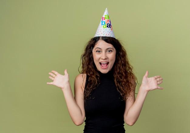 Młoda piękna kobieta z kręconymi włosami w czapce wakacje koncepcja szczęśliwy i podekscytowany przyjęcie urodzinowe nad światłem