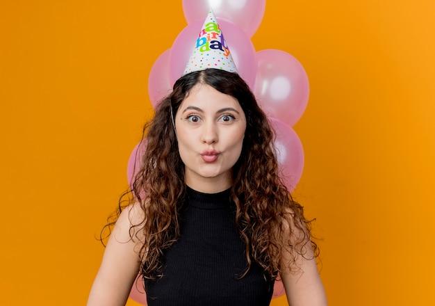 Młoda piękna kobieta z kręconymi włosami w czapce wakacje patrząc na canera zaskoczona koncepcja przyjęcie urodzinowe stojąc z balonami nad pomarańczową ścianą