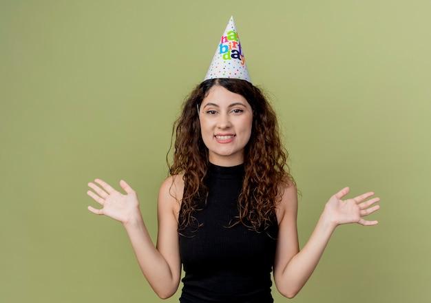 Młoda piękna kobieta z kręconymi włosami w czapce wakacje szczęśliwy i podekscytowany koncepcja przyjęcie urodzinowe stojący nad ścianą światła