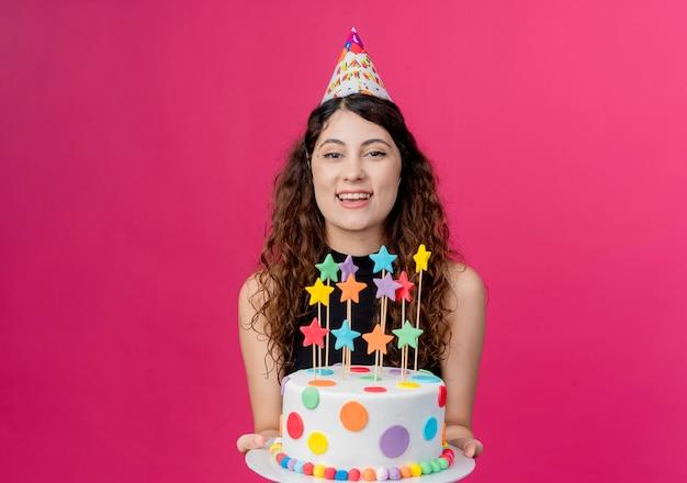 Młoda piękna kobieta z kręconymi włosami w czapce wakacje, trzymając szczęśliwy tort urodzinowy i wesoły koncepcja przyjęcie urodzinowe na różowo