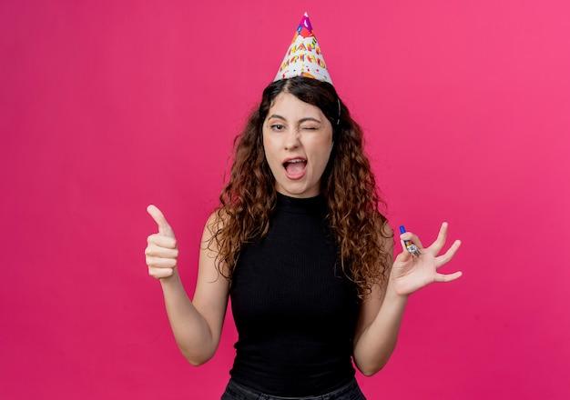 Młoda piękna kobieta z kręconymi włosami w czapce wakacje uśmiechnięta i mrugająca pokazując kciuki do góry koncepcja przyjęcia urodzinowego stojącego nad różową ścianą