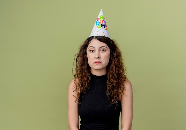 Młoda piękna kobieta z kręconymi włosami w czapce wakacje ze smutnym wyrazem twarzy koncepcja przyjęcie urodzinowe stojący nad pomarańczową ścianą