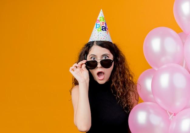 Młoda piękna kobieta z kręconymi włosami w czapce wakacyjnej trzyma balony z powietrzem, zdejmując okulary patrząc zaskoczony koncepcję przyjęcia urodzinowego stojącego nad pomarańczową ścianą