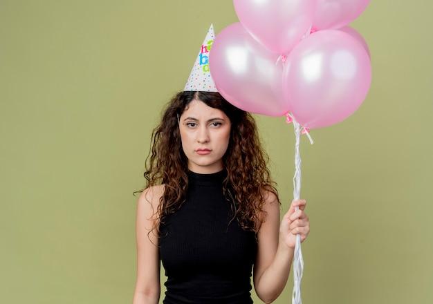 Młoda piękna kobieta z kręconymi włosami w czapce wakacyjnej, trzymając balony z marszczoną twarzą koncepcja przyjęcia urodzinowego stojącego nad ścianą światła