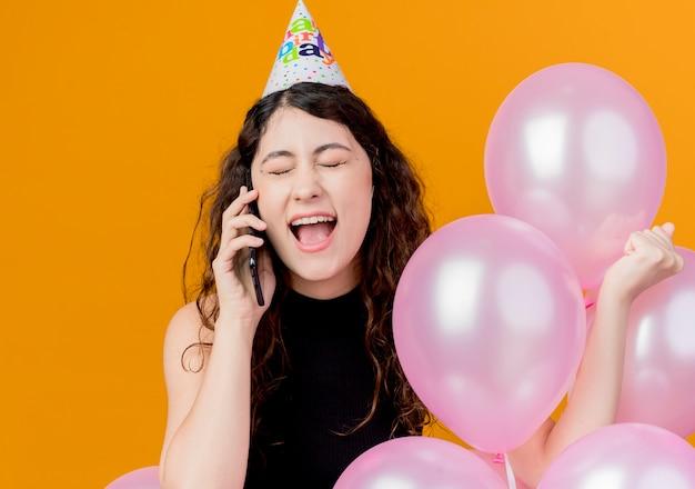 Młoda piękna kobieta z kręconymi włosami w czapce wakacyjnej trzymająca balony z powietrzem rozmawiająca przez telefon komórkowy szczęśliwa i podekscytowana koncepcja przyjęcia urodzinowego stojąca nad pomarańczową ścianą