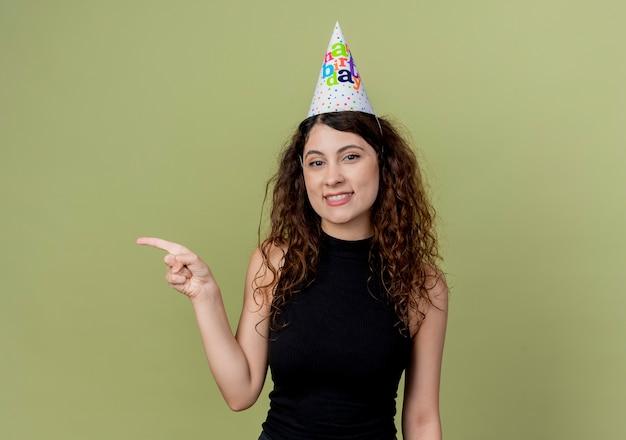 Młoda piękna kobieta z kręconymi włosami w czapce wakacyjnej wskazuje palcem w bok, uśmiechając się wesoło koncepcja przyjęcia urodzinowego stojącego nad jasną ścianą