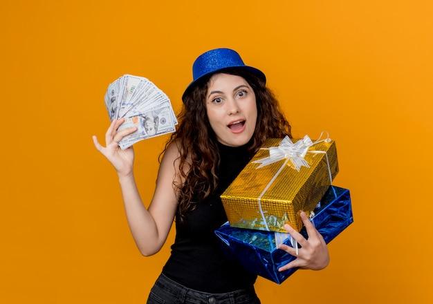 Młoda piękna kobieta z kręconymi włosami w kapeluszu strony, trzymając gotówkę i prezenty patrząc na canera szczęśliwy i podekscytowany stojąc nad pomarańczową ścianą