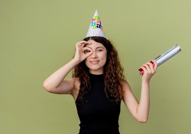 Młoda piękna kobieta z kręconymi włosami w świątecznej czapce pokazującej znak ok patrząc przez ten znak uśmiechnięta koncepcja przyjęcia urodzinowego stojącego nad jasną ścianą