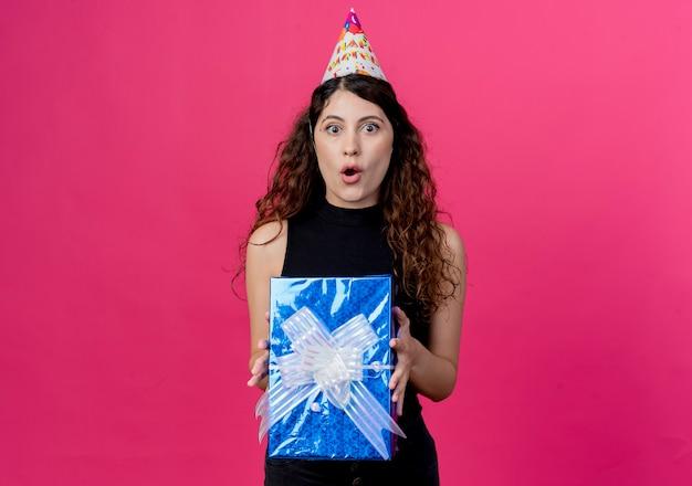 Młoda piękna kobieta z kręconymi włosami w świątecznej czapce trzyma pudełko, patrząc zaskoczony i zdumiony koncepcją przyjęcia urodzinowego stojącego nad różową ścianą