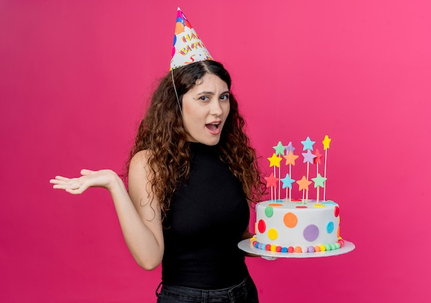 Młoda piękna kobieta z kręconymi włosami w świątecznej czapce trzyma tort urodzinowy mylić koncepcję przyjęcia urodzinowego stojącego nad różową ścianą