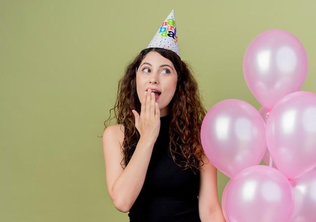 Młoda piękna kobieta z kręconymi włosami w świątecznej czapce trzymając balony z powietrza patrząc na bok zaskoczony i szczęśliwy w świetle
