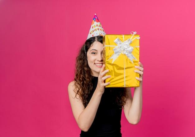 Młoda piękna kobieta z kręconymi włosami w świątecznej czapce, trzymając pudełko na prezent urodzinowy, uśmiechając się wesoło koncepcja przyjęcie urodzinowe stojąc nad różową ścianą