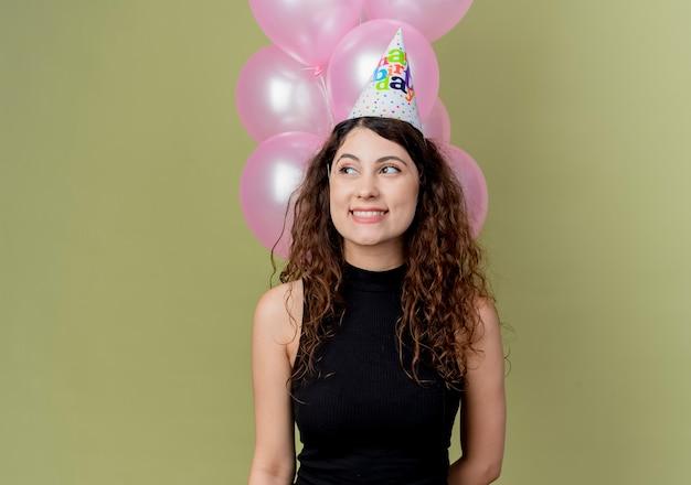 Młoda piękna kobieta z kręconymi włosami w świątecznej czapce trzymająca balony z powietrzem patrząc na bok, uśmiechnięta wesoło z radosną twarzą świętująca przyjęcie urodzinowe stojąc nad jasną ścianą
