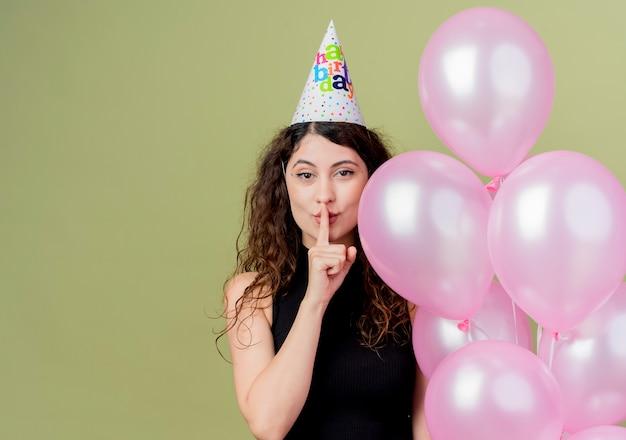 Młoda piękna kobieta z kręconymi włosami w świątecznej czapce trzymająca balony z powietrzem wykonująca gest ciszy z palcem na ustach wyglądająca pewnie na przyjęcie urodzinowe stojąca nad jasną ścianą