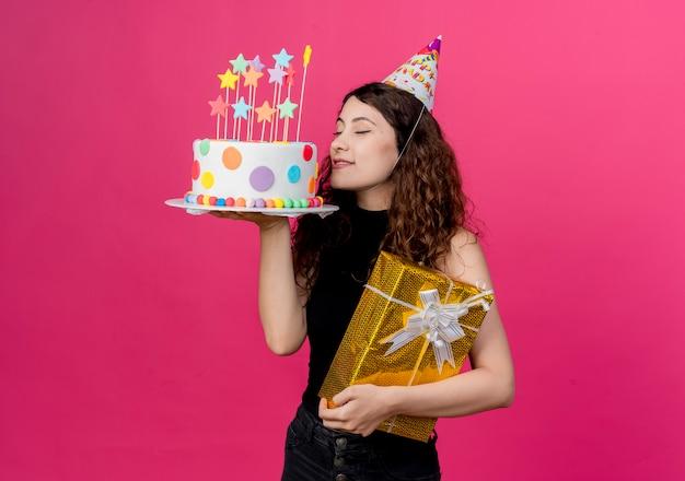Młoda piękna kobieta z kręconymi włosami w świątecznej czapce trzymająca tort urodzinowy i pudełko na szczęśliwe i pozytywne przyjęcie urodzinowe stojąca z zamkniętymi oczami nad różową ścianą