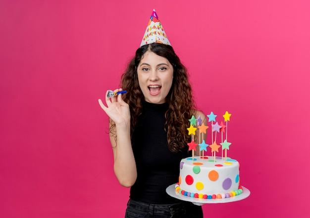 Młoda piękna kobieta z kręconymi włosami w świątecznej czapce trzymająca tort urodzinowy szczęśliwa i podekscytowana, uśmiechnięta wesoło koncepcja przyjęcia urodzinowego stojącego nad różową ścianą
