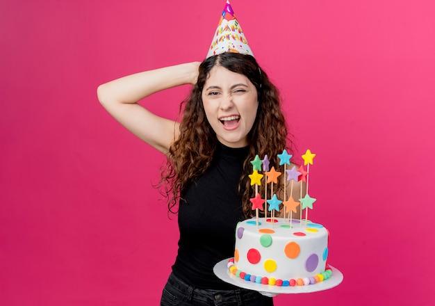 Młoda piękna kobieta z kręconymi włosami w świątecznej czapce trzymająca tort urodzinowy, uśmiechnięta wesoło, wyglądająca na szczęśliwą i radosną koncepcję przyjęcia urodzinowego, stojąca nad różową ścianą