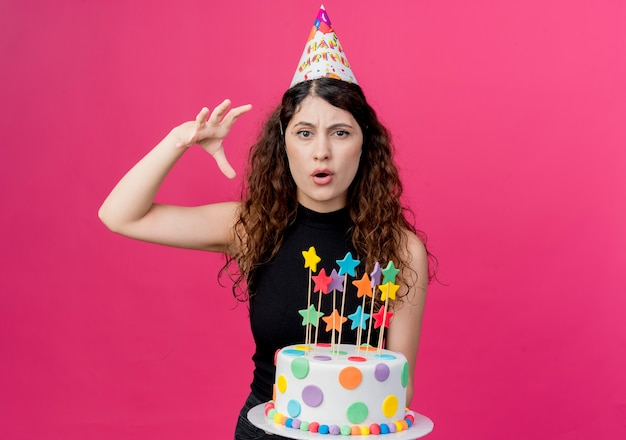 Młoda piękna kobieta z kręconymi włosami w świątecznej czapce trzymającej tort urodzinowy niezadowolona koncepcja przyjęcia urodzinowego stojącego nad różową ścianą