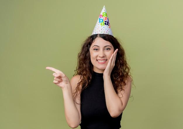 Młoda piękna kobieta z kręconymi włosami w świątecznej czapce, uśmiechnięta radośnie, wskazująca palcem na bok koncepcja przyjęcia urodzinowego stojącego nad jasną ścianą