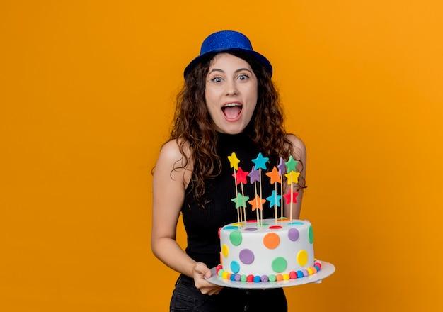 Młoda piękna kobieta z kręconymi włosami w świątecznym kapeluszu, trzymając tort urodzinowy szczęśliwy i podekscytowany stojąc nad pomarańczową ścianą