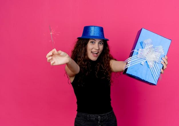 Młoda piękna kobieta z kręconymi włosami w świątecznym kapeluszu, trzymająca pudełko na prezent urodzinowy i brylant szczęśliwa i podekscytowana koncepcja przyjęcia urodzinowego stojąca nad różową ścianą
