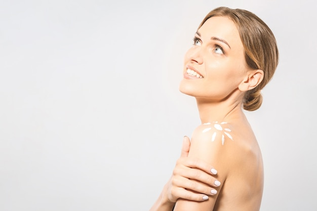 Młoda piękna kobieta z kremem do opalania w kształcie słońca. ładna kobieta gotowa do leczenia opalenizny. sunscreen balsam do opalania opierając się na ramieniu kobiety. na białym tle