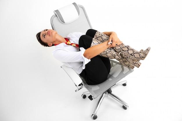Młoda piękna kobieta z krótkimi ciemnymi włosami, makijażem w białej koszuli, czarnymi spodniami, długimi skórzanymi wężowymi butami, z czerwonym szalikiem, zegarkiem i pięknym makijażem siedzi na białym krześle komputerowym i marzy
