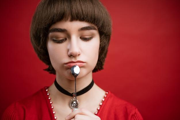 Młoda piękna kobieta z krótkimi włosami i zamyślonym spojrzeniem, trzymając łyżkę w dłoni w pobliżu twarzy. zbliżenie na czerwonym tle.