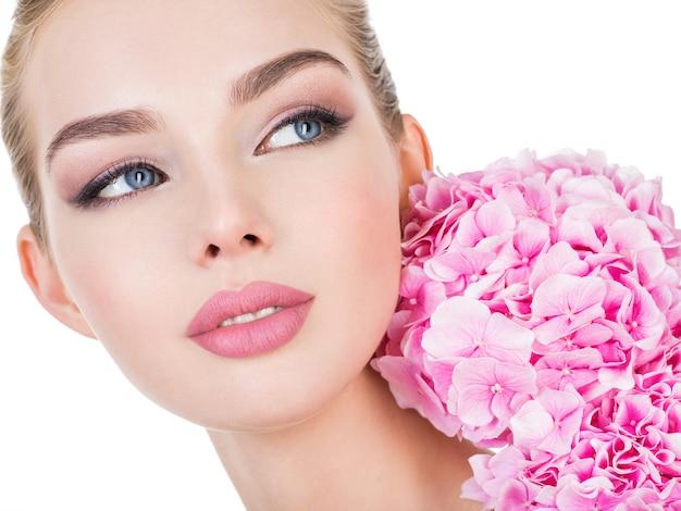 Młoda piękna kobieta z kwiatami w pobliżu twarzy.