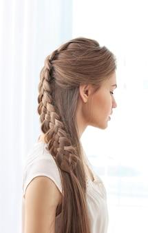 Młoda piękna kobieta z ładną fryzurą warkocza na światło