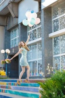 Młoda piękna kobieta z latającymi wielokolorowymi balonami skaczącymi po mieście