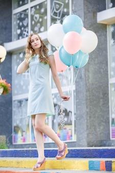 Młoda piękna kobieta z latającymi wielokolorowymi balonami w mieście