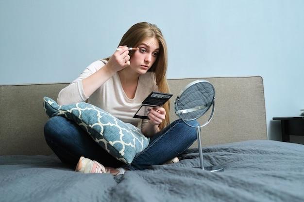 Młoda piękna kobieta z lustrem robi makijaż malowanie oczu pomponem, siedząc w domu na łóżku