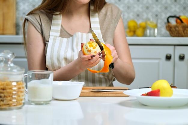Młoda piękna kobieta z owocami w kuchni, kobieta siedzi przy stole i czyszczenie pomarańczy. kobieta blogerka kulinarna gotująca sałatkę owocową w aparacie