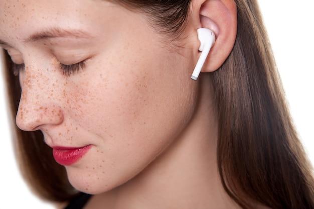 Młoda piękna kobieta z piegami i bezprzewodowymi słuchawkami na uszach. strzał studio.