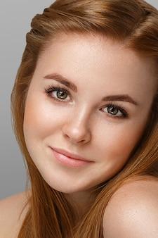 Młoda piękna kobieta z piegami portret studio hipster pozowanie. na szarym tle