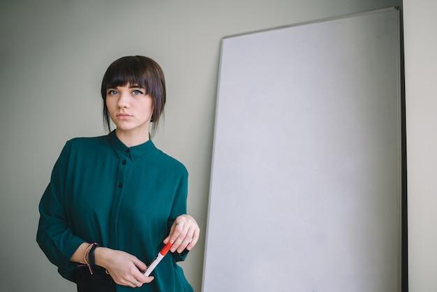Młoda piękna kobieta z pisania markerem lub rysowania stoi na tablicy. pomysł na biznes