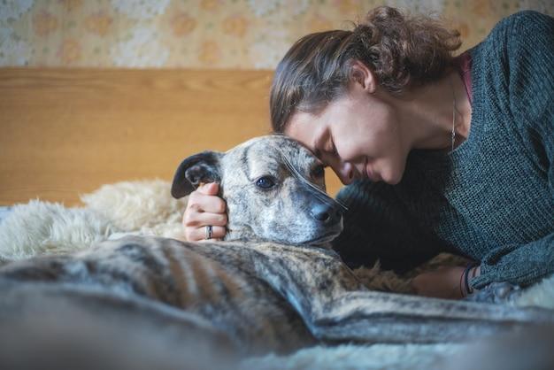 Młoda piękna kobieta z psem na łóżku, łeb w łeb, najlepsi przyjaciele i zwierzę domowe opieki pojęcie