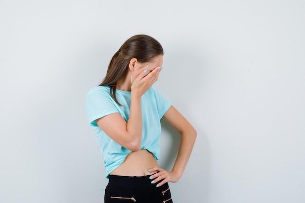 Młoda piękna kobieta z ręką na twarzy w t-shirt i patrząc smutno. przedni widok.
