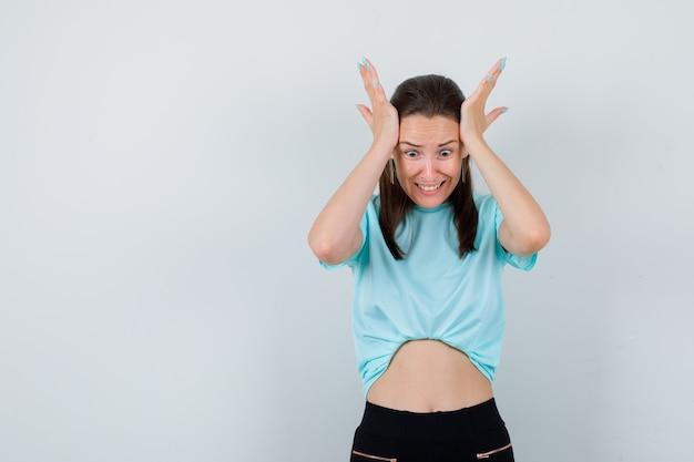 Młoda piękna kobieta z rękami na głowie w koszulce, spodniach i patrząc sfrustrowany, widok z przodu.