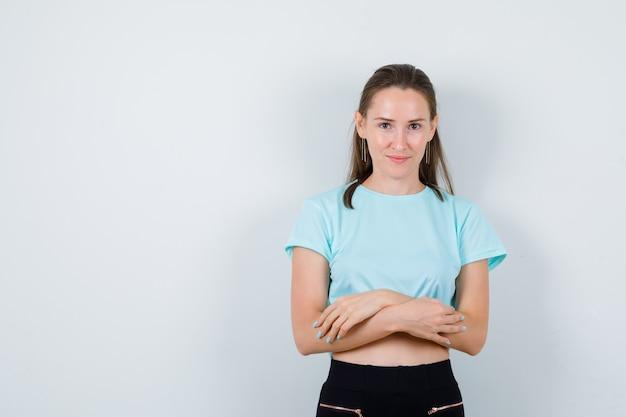 Młoda piękna kobieta z rękoma złożonymi w t-shirt i patrząc wesoło, widok z przodu.